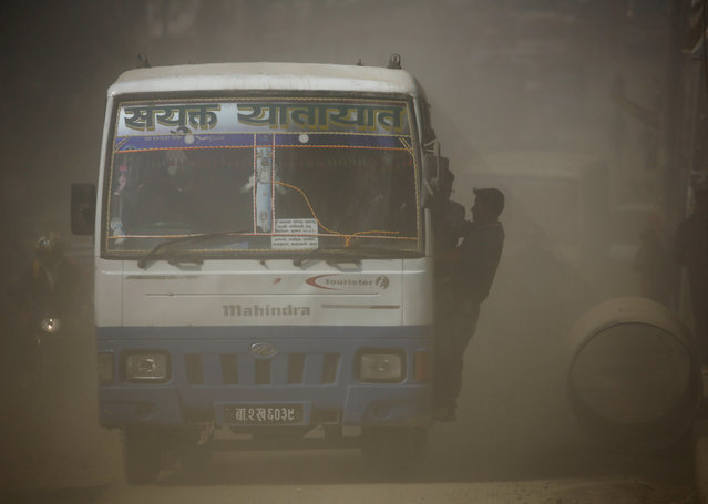 A passenger bus travels along a dusty road in Kathmandu, Nepal February 27, 2017. (Photo by Navesh Chitrakar/Reuters)