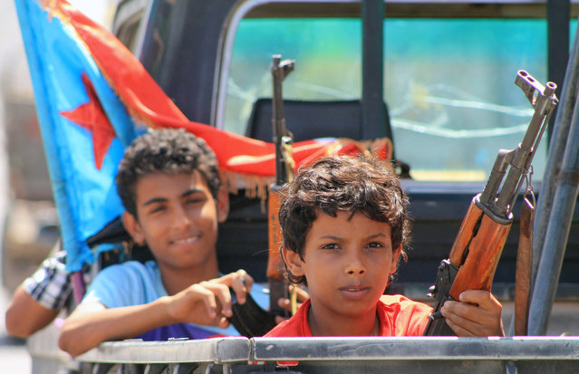 Armed Yemeni children sit in the back of a pick up truck with fighters loyal to Yemen's Saudi-backed President Abedrabbo Mansour Hadi in the Dar saad neighbourhood of the southern Yemeni city of Aden on May 10, 2015, as they continue to battle Shiite Huthi rebels. (Photo by Saleh Al-Obeidi/AFP Photo)