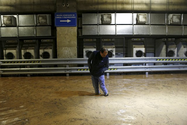A man is seen inside an underground flooded parking in Santiago, April 17, 2016. (Photo by Ivan Alvarado/Reuters)