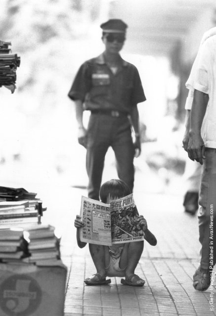 1973: A Vietnamese child reads a comic bought for him by a Vietnamese soldier