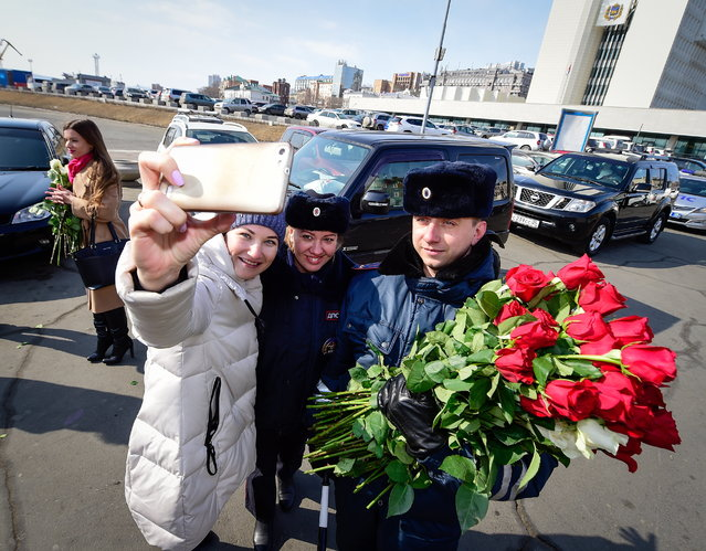 A female driver takes a selfie with traffic policemen who have congratulated her on upcoming International Women's Day in the citys Central Square in Vladivostok, Russia on March 7, 2017. Policemen in several Russian cities pulled over women on Tuesday and Wednesday, which is International Women's Day – but instead of writing tickets, they handed out roses. March 8 is similar to Valentine's Day in Russia, and it has become a day dedicated to buying women flowers and pampering them. Photos capture quite the spectrum of reactions. (Photo by Yuri Smityuk/TASS via Getty Images)