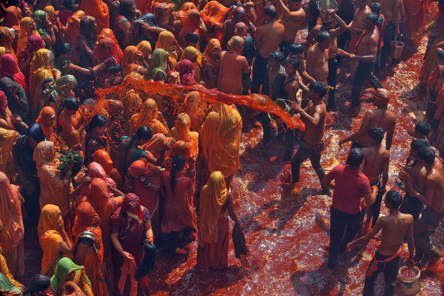 """A man throws coloured water during """"Huranga"""", a game played between men and women a day after Holi, at Dauji temple near Mathura, March 14, 2017. (Photo by Cathal McNaughton/Reuters)"""