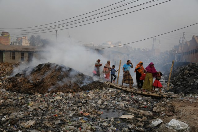 In this Monday, February 6, 2017 photo, Bangladeshi people walk across a temporary bridge as smoke emits from tannery waste at the highly polluted Hazaribagh tannery area in Dhaka, Bangladesh. (Photo by A.M. Ahad/AP Photo)