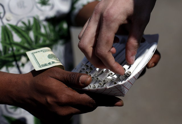 An entrepreneur sells pre-rolled joints during 420 celebrations at Hippie Hill in Golden Gate Park in San Francisco, Calif., on Sunday, April 20, 2014. (Photo by  Sarah Rice/AP Photo/San Francisco Chronicle)