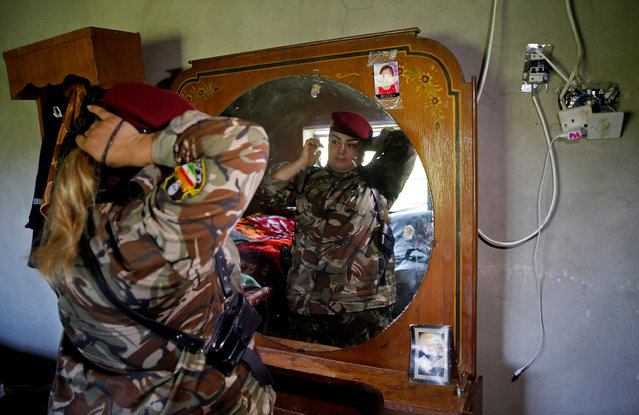 Iraqi Kurdish female fighter Haseba Nauzad, 24, looks at a mirror as she adjusts her clothes in a bedroom at a site near the frontline of the fight against Islamic State militants in Nawaran near Mosul, Iraq April 20, 2016. (Photo by Ahmed Jadallah/Reuters)