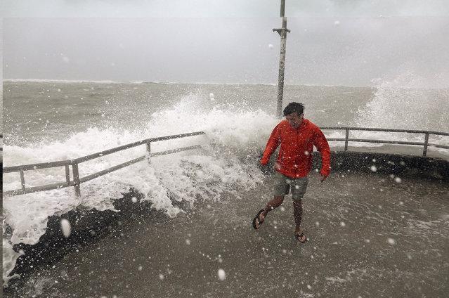 Brandon Ennis runs away from waves caused by Hurricane Dorian crashing over the jetty of the Jupiter inlet, Tuesday, September 3, 2019, in Jupiter, Fla. (Photo by Joe Cavaretta/South Florida Sun-Sentinel via AP Photo)