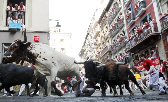 A runner falls in front of Jandilla fighting bulls at the Mercaderes curve during the first running of the bulls of the San Fermin festival in Pamplona, northern Spain, July 7, 2015. (Photo by Susana Vera/Reuters)