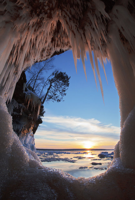 """Winner of the National Park Foundation's photo contest; Second place. Apostle Islands National Lakeshore, Wisconsin. """"In late December, a friend and I launched a canoe from the pack ice at Meyer's Beach, gateway to the mainland sea caves in the Apostle Islands National Lakeshore. We broke skim ice and dodged ice bergs out to the caves, and we were well rewarded for our efforts. I made the image from the canoe, through a port hole as the sun set across Mawikwe Bay"""", DeWitt said. (Photo by Michael DeWitt)"""