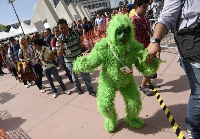 Jerk Salazar, of Monterey Calif, waits in line dressed as the Grinch on day 1 of Comic-Con International on Thursday, July 9, 2015, in San Diego, Calif. (Photo by Chris Pizzello/Invision/AP Photo)