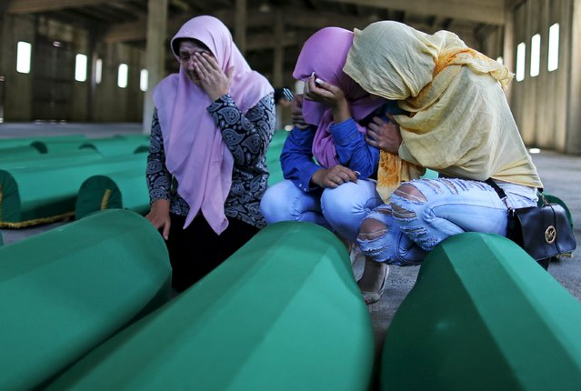 Women cry next to coffins of their relatives who were victims of the 1995 Srebrenica massacre, at the Memorial Center in Potocari, Bosnia and Herzegovina, July 10, 2015. The bodies of the 136 recently identified victims of Srebrenica massacre will be transported to the memorial centre in Potocari where they will be buried on July 11, the anniversary of the massacre when Bosnian Serb forces slaughtered 8,000 Muslim men and boys and buried them in mass graves in Europe's worst massacre since World War Two. (Photo by Dado Ruvic/Reuters)