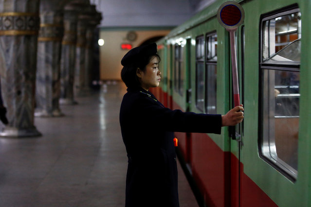 A railway worker gives a signal as the train leaves a subway station visited by foreign reporters in central Pyongyang, North Korea on April 14, 2017. (Photo by Damir Sagolj/Reuters)