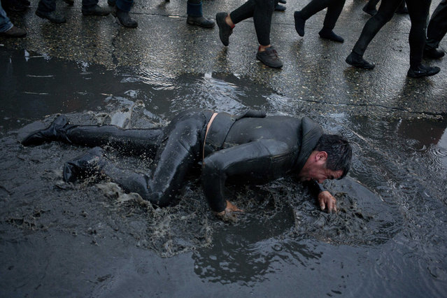 A diver creeps in puddle on the street during a protest march by shellfish divers in Chiloe Island, Chile, Thursday, May 12, 2016. The government has declared an emergency zone along Chile's south as it deals with the algae bloom known as red tide, which kills fish with a toxin that paralyzes the central nervous system, and small-scale fishermen are demanding compensation. (Photo by Esteban Felix/AP Photo)