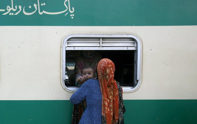 "A woman passes a baby boy to her relative from a window of the train that will take them back to their hometown, ahead of the Muslim Eid al-Fitr festival, at the Cantonment railway station in Karachi, Pakistan, July 12, 2015. The words on (top left) read in Urdu ""Pakistan railway"". (Photo by Akhtar Soomro/Reuters)"