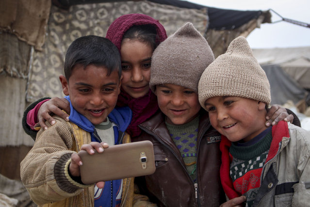 Internally Displaced Syrian kids, fled from their homes due to the Assad Regime forces' attacks on civilians and siege for more than 6 years, pose for a photo as they try to live at a makeshift tent camp, in Eastern Ghouta of Damascus, Syria on April 19, 2017. (Photo by Kaled Abu Jaafer/Anadolu Agency/Getty Images)