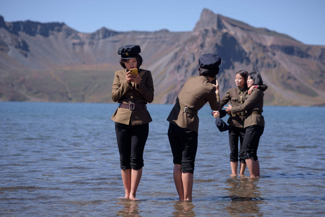 "In a photo taken on September 11, 2019, North Korean students pose for photos in Chonji lake, or ""Heaven lake"", as they visit the crater of Mount Paektu, near Samjiyon. Mount Paektu has long been considered the spiritual birthplace of the Korean nation and is a place of pilgrimage for tens of thousands of North Koreans every year, who are trained from birth to revere their leaders. Every year 100,000 North Koreans or more are taken on study tours to the camp, the mountain, and nearby revolutionary sites where relics of operations are preserved. Dressing in khaki uniforms said to resemble guerrillas' outfits and carrying red flags, they march to the summit of the volcano. (Photo by Ed Jones/AFP Photo)"