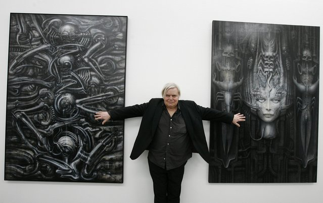 "In this June 29, 2007 file picture  Swiss artist H.R. Giger  poses with two of his works at the art museum in Chur, Switzerland.  H.R. Giger, who designed the creature in Ridley Scott's sci-fi horror classic ""Alien"", has died at age 74 from injuries suffered in a fall. Sandra Mivelaz, administrator of the H.R. Giger museum in Chateau St. Germain told The Associated Press Tuesday May 13, 2014  that Giger had died in a hospital the day before.  Giger  received a 1979 Academy Award for special effects in ""Alen"". (Photo by Arno Balzarini/AP Photo/Keystone)"
