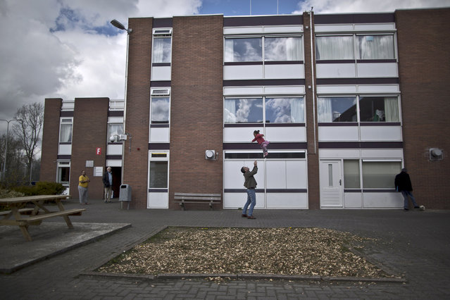 In this Friday, April 8, 2016 photo, a migrant plays with a girl at the former prison of Westlingen in Heerhugowaard northwestern Netherlands. The Dutch government has let Belgium and Norway put prisoners in its empty cells and now, amid the huge flow of migrants into Europe, several Dutch prisons have been temporarily pressed into service as asylum seeker centers. (Photo by Muhammed Muheisen/AP Photo)