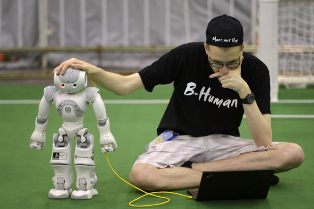"A member from a German team adjusts a humanoid robot during the 2015 Robocup finals in Hefei, Anhui province, July 22, 2015. The Robocup, or ""Robot Soccer World Cup"", is an annual international robotics competitions which is held between July 17 - 23 this year in China's Hefei. (Photo by Reuters/Stringer)"