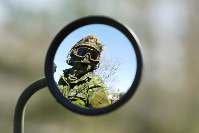 A Canadian Forces member is seen in a mirror while riding in a Light Armoured Vehicle (LAV) through the flooded Constance Bay area in Ottawa, Ontario, Canada, April 30, 2019. (Photo by Chris Wattie/Reuters)