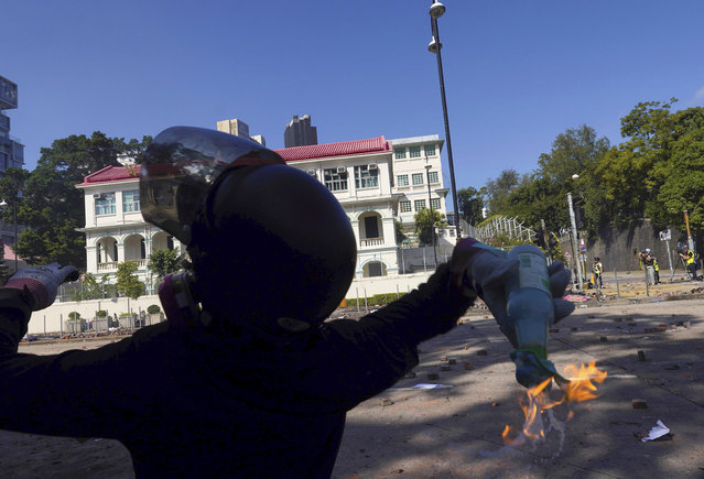 A protestor prepares to hurl a molotov cocktail at police at Hong Kong Polytechnic University in Hong Kong, Sunday, November 17, 2019. Police have fired tear gas at protesters holding out at Hong Kong Polytechnic University as overnight clashes resumed in the morning. (Photo by Vincent Yu/AP Photo)