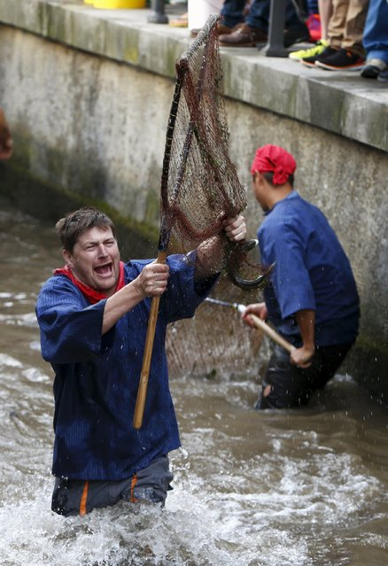 Fisherman Stefan Albrecht reacts as he catches a trout in a small river while celebrating Fischertag (Fisherman's Day) in downtown Memmingen, southern Germany, July 25, 2015. (Photo by Michaela Rehle/Reuters)