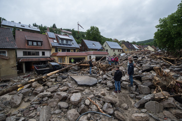People stand on an avalanche of debris covering a street in Braunsbach, Germany, Monday, May 30, 2016. Authorities said three people are suspected to have died as floods struck Germany. Southern and western Germany, along with other parts of Europe, experienced heavy rainstorms over the weekend. (Photo by Marijan Murat/DPA via AP Photo)