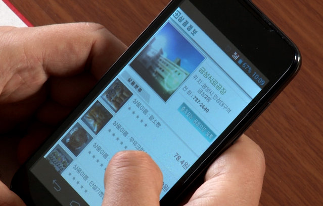 In this April 22, 2015, image taken from APTN, a man uses his smartphone to demonstrate how to use North Korea's new online shopping site,. North Korean officials have unveiled a mobile-friendly online shopping site that could give the nation its first taste of what many around the world have long seen as a mundane fact of modern life and provide local consumers with a rare opportunity to shop around for the best bargains. (Photo by AP Photo/APTN)