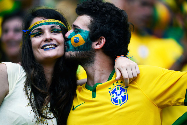 Brazil fans kiss prior to the Group A football match between Brazil and Mexico in the Castelao Stadium in Fortaleza during the 2014 FIFA World Cup on June 17, 2014. (Photo by Odd Andersen/AFP Photo)