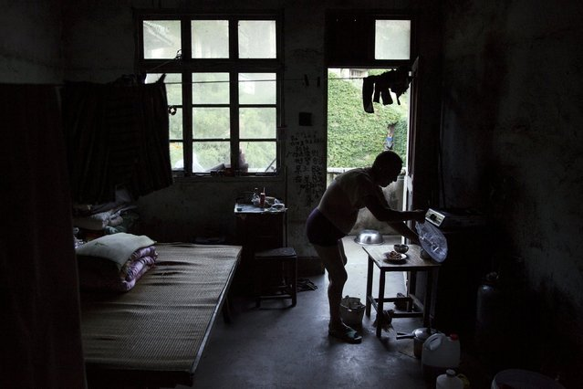 Sun Ayue, one of very few residents of the abandoned fishing village of Houtouwan on the island of Shengshan prepares dinner at the room where he lives July 25, 2015. (Photo by Damir Sagolj/Reuters)