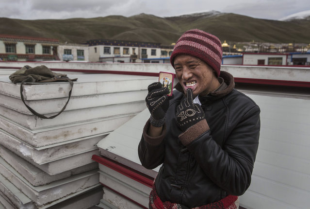A Tibetan nomad checks a fake gold cap that he had put on a tooth by a street dentist during a break from harvesting cordycep fungus on the 15th day of Saka Dawa, the holiest day of the Buddhist calendar on May 21, 2016 at the Sershul Monastery on the Tibetan Plateau in the Garze Tibetan Autonomous Prefecture of Sichuan province. (Photo by Kevin Frayer/Getty Images)