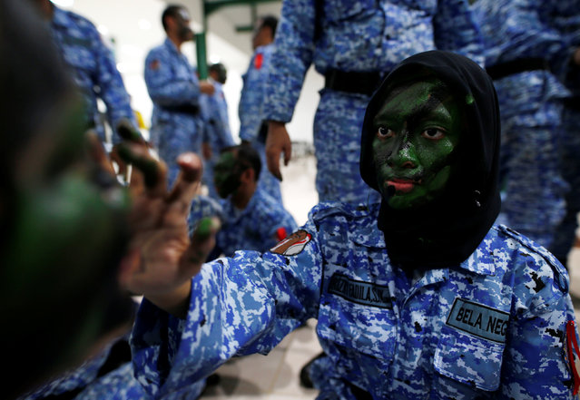 "A female participant of the Bela Negara – ""defend the nation"" – programme applies camouflage face paint on another participant's face at a training centre in Rumpin, Bogor, West Java, Indonesia June 2, 2016. (Photo by Darren Whiteside/Reuters)"