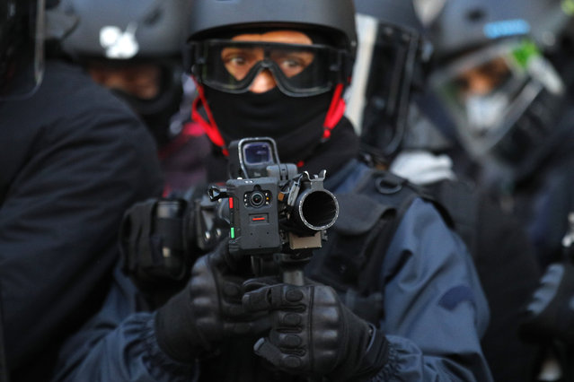 A police officer holds a high-velocity rubber bullets for crowd control equipped with a camera during a yellow vest protest Saturday, February 2, 2019 in Paris. France's yellow vest protesters are taking to the streets to keep pressure on French President Emmanuel Macron's government, for the 12th straight weekend of demonstrations. This week, demonstrators in the French capital are planning to pay tribute to the yellow vests injured during clashes with police. (Photo by Francois Mori/AP Photo)