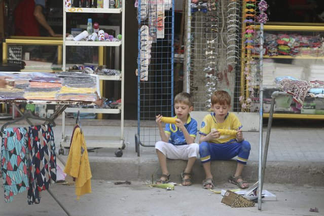 Two boys sit on a pavement as they eat corn in Aleppo's eastern district of Tariq al-Bab, Syria, August 1, 2015. (Photo by Abdalrhman Ismail/Reuters)