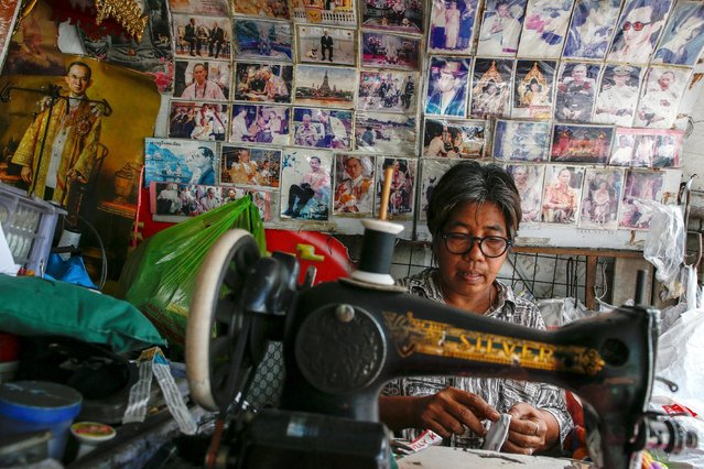 A woman works on a sewing machine on a street in front of a wall decorated with photographs of Thailand's King Bhumibol Adulyadej in Bangkok, Thailand, June 2, 2016. (Photo by Athit Perawongmetha/Reuters)