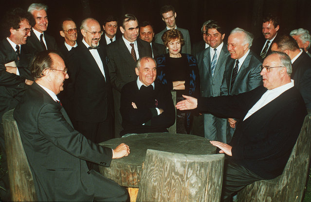 The July 17, 1990 file photo shows Soviet President Mikhail Gorbachev, center,sitting with West German Chancellor Helmut Kohl, right, and German Foreign Minister Hans-Dietrich Genscher at a table in the garden of the guest house in Archiz during a break in their talks on the discussion of NATO-membership of United Germany, the most difficult topic in the negotiations to German unification. In the background are German government spokesman Hans Klein, West German Finance Minister Theo Waigel, sixth from left, Raissa Gorbacheva, Soviet Finance Minister Pavlov and Soviet Foreign Minister Eduard Shevardnadze, third from right. The other persons are unidentified delegation members. (Photo by Roberto Pfeil/AP Photo)