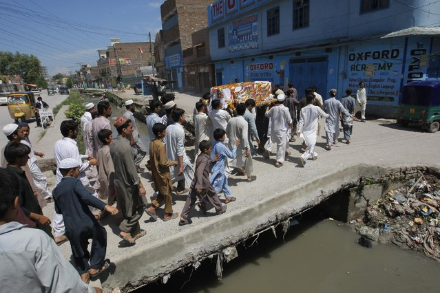 People carry the coffin of a boy reportedly drowned during a flooding, on their way for a burial in Peshawar, Pakistan, Monday, July 27, 2015. (Photo by Muhammad Sajjad/AP Photo)