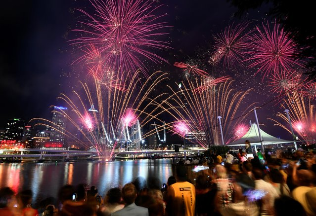 Crowds watch fireworks display during New Year's Eve celebrations in Brisbane, Australia on January 1, 2020. (Photo by Dan Peled/AAP Image via Reuters)