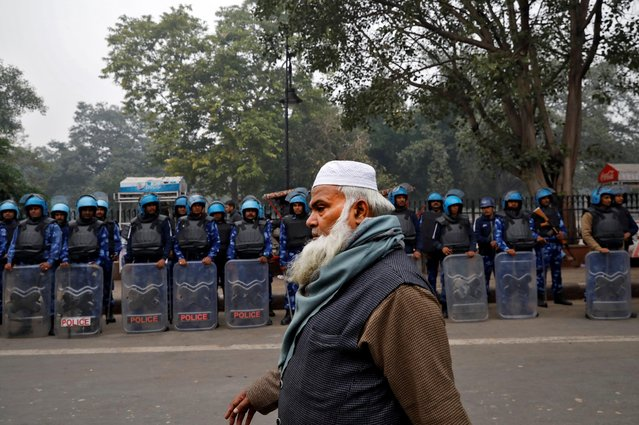 A Muslim man walks past Rapid Action Force personnel during a protest against a new citizenship law, in Delhi, December 19, 2019. (Photo by Danish Siddiqui/Reuters)