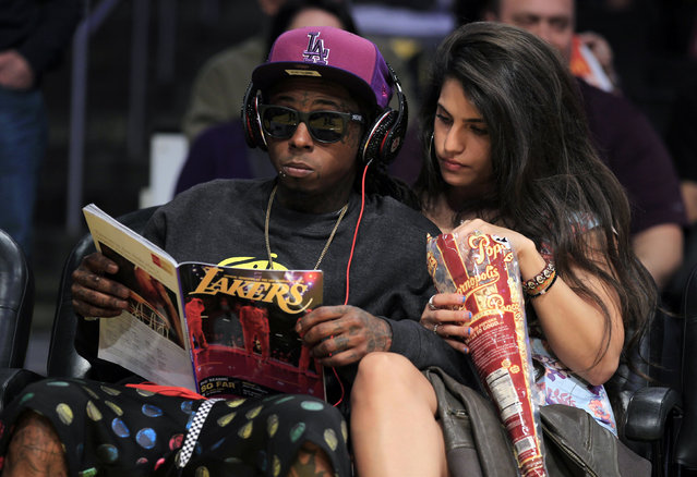 Lil Wayne and his friend Dhea watch the Lakers play the Heat in Los Angeles, March 2012. (Photo by Lucy Nicholson/Reuters)