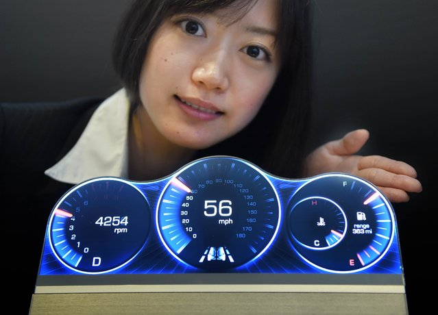 An employee of Japan's electronics giant Sharp introduces a prototype model of the newly developed free-form LCD display at its head office in Tokyo on July 7, 2014. The free-form display can be shaped into various patterned models such as elliptical shape using Sharp's IGZO technology. (Photo by Toru Yamanaka/AFP Photo)