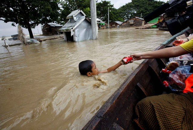 In this August 7, 2015, file photo, a boy swimming in water receives foods from private donors near half-submerged residences in Nyaung Tone, in the Irrawaddy Delta, southwest of Yangon, Myanmar. Myanmar says the number of people affected by flooding nationwide is approaching 1 million, with waters in the low-lying southwestern region inundating homes and forcing villagers into temporary shelters. (Photo by Khin Maung Win/AP Photo)