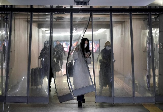 People wearing masks walk through an underground passage to the subway in Beijing, China on January 21, 2020. The death toll from a mysterious flu-like virus in China climbed to six as new cases surged beyond 300 and authorities fretted about the added risk from millions of Chinese traveling for the Lunar New Year holiday. (Photo by Jason Lee/Reuters)