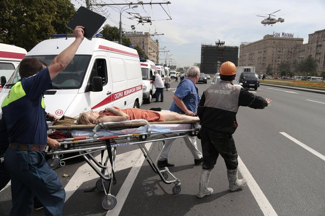 Paramedics carry an injured woman out from a subway station after a rush-hour subway train derailment, to be transported by a medical helicopter in Moscow, Russia, on Tuesday, July 15, 2014. (Photo by Ivan Sekretarev/AP Photo)