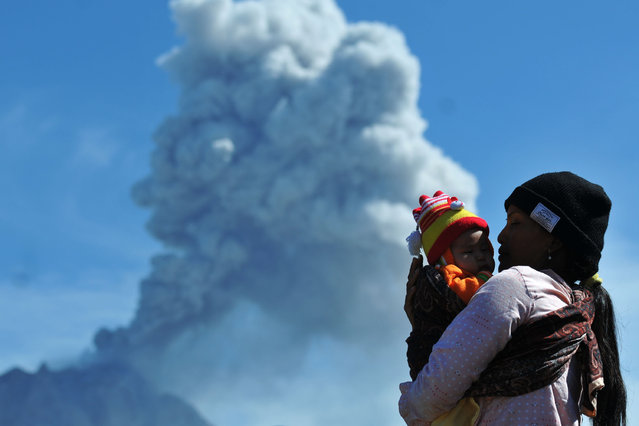 A woman carries her child as she watches Mount Sinabung volcano spewing thick volcanic ash, as seen from Karo on July 21, 2017. Sinabung roared back to life in 2010 for the first time in 400 years, after another period of inactivity it erupted once more in 2013, and has remained highly active since. (Photo by Gatha Ginting/AFP Photo)