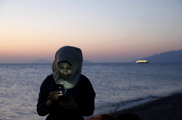 A Syrian refugee sends text messages to relatives moments after arriving at a beach on the Greek island of Kos, August 12, 2015. (Photo by Yannis Behrakis/Reuters)