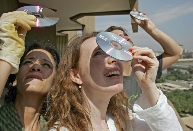 An Iraqi woman and foreigners use  pair of compact discs as a filter to watch the partial solar eclipse in war-torn Baghdad, 29 March 2006. Without access to proper equipment to protect their eyes from the sun's rays, eclipse watchers in Iraq used makeshift filters.  The moon blotted out the sun over northwest Africa early Wednesday, turning day into night in a total solar eclipse as it swept a shadowy path from the outer tip of Brazil to the steppes of Mongolia. (Photo by Hassan Ammar/AFP Photo)