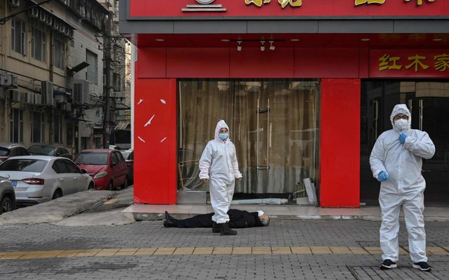 This photo taken on January 30, 2020 shows officials in protective suits checking on an elderly man wearing a facemask who collapsed and died on a street near a hospital in Wuhan. AFP journalists saw the body on January 30, not long before an emergency vehicle arrived carrying police and medical staff in full-body protective suits. The World Health Organization declared a global emergency over the new coronavirus, as China reported on January 31 the death toll had climbed to 213 with nearly 10,000 infections. (Photo by Hector Retamal/AFP Photo)
