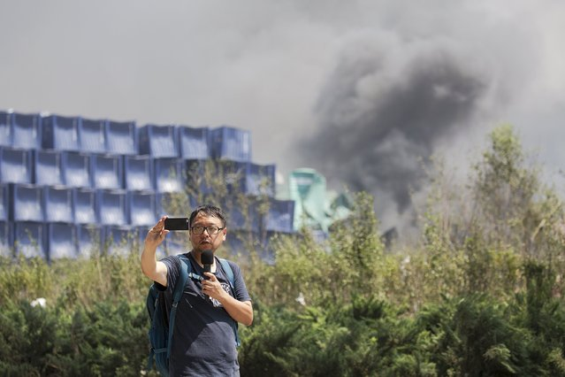 A man uses a mobile phone and a microphone to report from the explosion site in Binhai new district in Tianjin, China August 13, 2015. The death toll from two huge explosions that tore through an industrial area in the northeastern Chinese port of Tianjin more than doubled to 44, the official Xinhua news agency said on Thursday. (Photo by Damir Sagolj/Reuters)