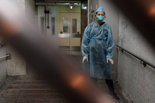 A personnel wearing protective suit waits near an entrance at the Cheung Hong Estate, a public housing estate during evacuation of residents in Hong Kong, Tuesday, February 11, 2020. The Centre for Health Protection of the Department of Health evacuated some residents from the public housing estate after two cases of novel coronavirus infection to stop the potential risk of further spread of the virus. (Photo by Kin Cheung/AP Photo)