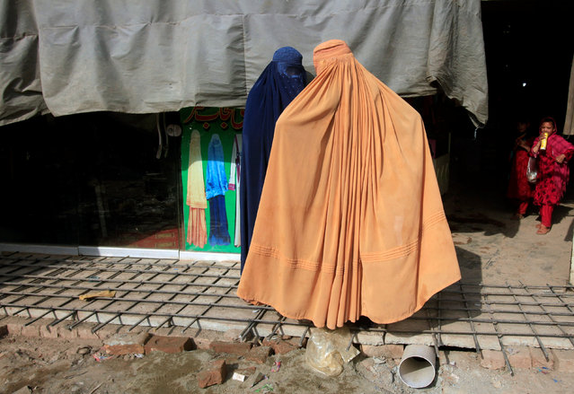 Afghan women, clad in burqas, stand outside a shop at a market in Peshawar, Pakistan June 29, 2016. (Photo by Fayyaz Hussain/Reuters)